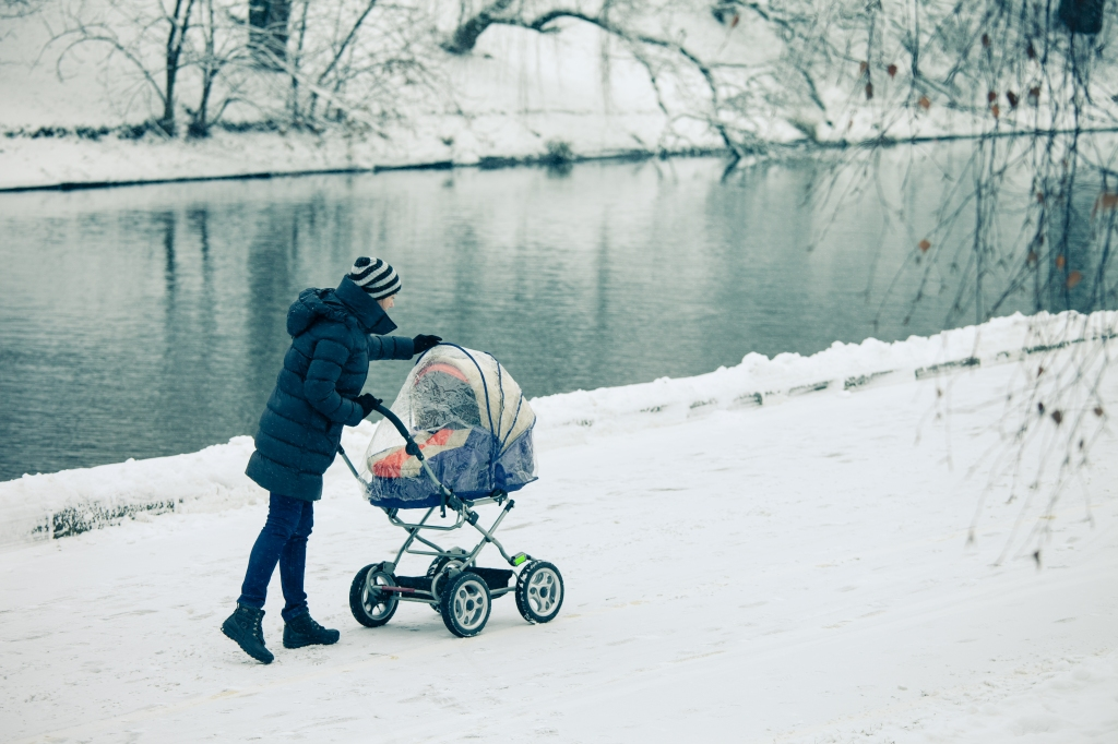 Woman with a baby stroller on a walk in the park
