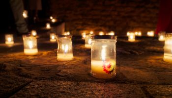 Close-Up Of Illuminated Tea Light Candles In Church