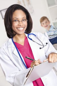 Happy Doctor Writing Something With Young Patient Behind Her