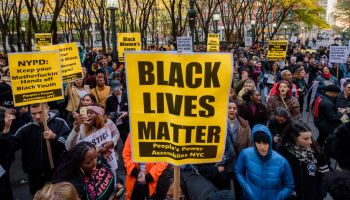 Participants holding BLACK LIVES MATTER protest signs at the...